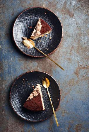 Two pieces of chocolate cake on black plates, top view. Фото со стока
