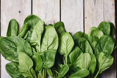 Green spinach leaves on a wooden surface, top view.