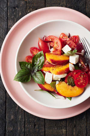 Salad with tomatoes, peach, red onion, cheese and basil. Top view. Фото со стока