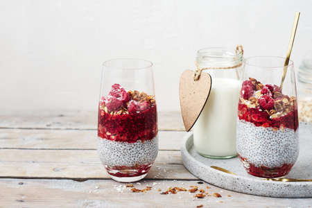 Two glasses of chia pudding with granola and raspberries. Фото со стока