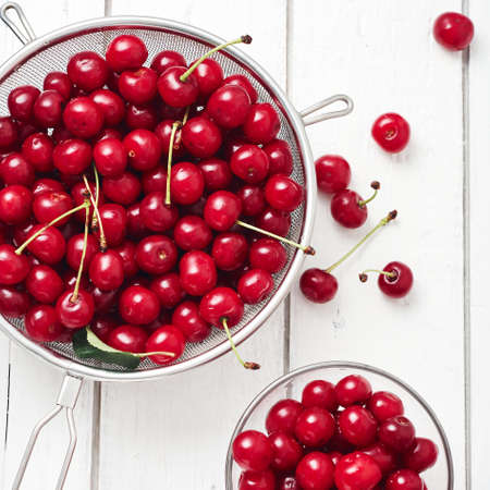 Fresh cherries on a white wooden background. Фото со стока