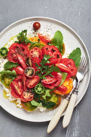 Tomato salad with arugula and ricotta cheese. Фото со стока