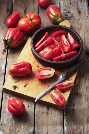 Fresh tomatoes for making tomato sauce on a wooden cutting board. Фото со стока