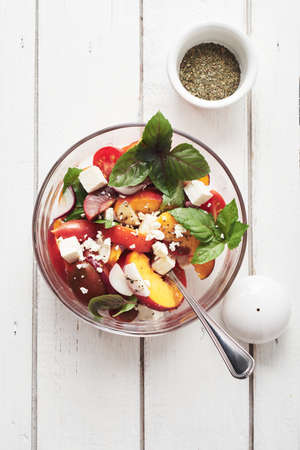 Salad with tomatoes, peach, red onion, feta cheese and basil. Top view.