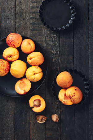 Fresh apricots on a dark wooden table, top view. Фото со стока