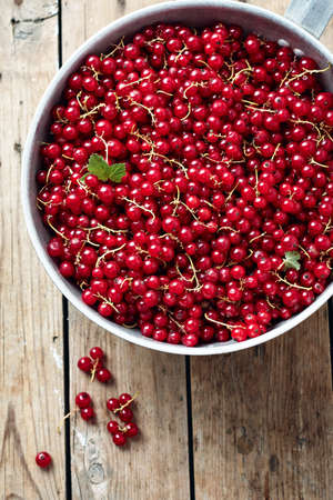 Red currants in a bowl on a wooden table, top view. Фото со стока