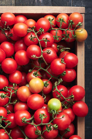Red cherry tomatoes in a wooden box. Harvest tomatoes, top view.