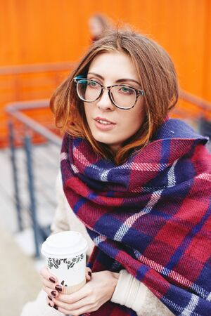 Girl in blanket scarf with coffee sitting in puplic space