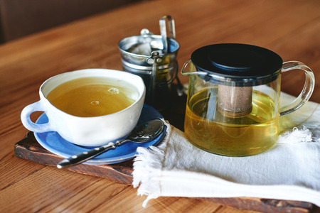 the brewer: Pottery mug and teapot with green tea on wooden table Stock Photo