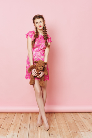 Fashion photo of young girl posing with Teddy bear over pink background in studio Stock Photo