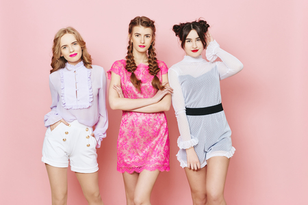 Fashion photo of three young girl posing over pink background in studio