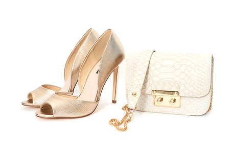 Golden high heel shoes with small stylish handbag isolated on white background