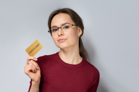 Young woman in red jumper in glasses holding gold gard isolated on gray background