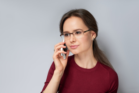 Young woman in red jumper in glasses talking phone isolated on gray background Stock Photo