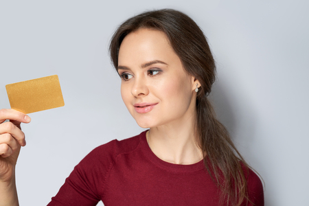 Young beautiful woman in red jumper holding gold gard isolated on gray background