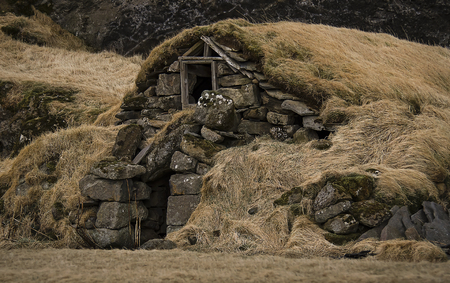 Old stone house destroyed ancient Viking overgrown with yellow dry grass