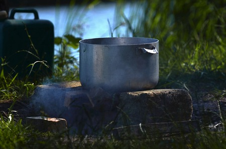 At a picnic near the river, a large metal pan in which fish soup is prepared against the background of green grass and smoke stands on the stones in Ukraine