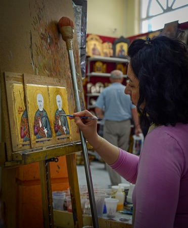 Woman painter paints icons in icon shop