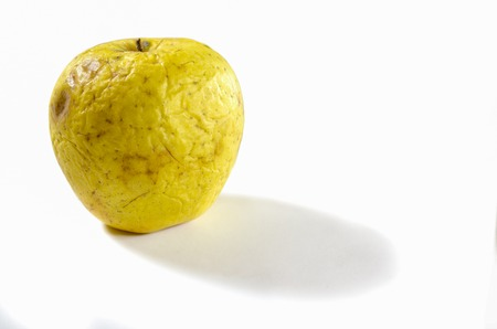 An old wrinkled apple lying on a white background. isolated Stock Photo - 114191964