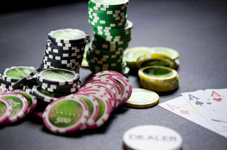 On the black table lie poker chips, cards and a dealer chip Imagens