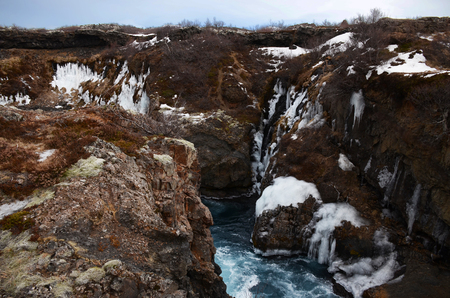 Glacial river of Iceland from blue water amid lava fields and blue winter sky 写真素材