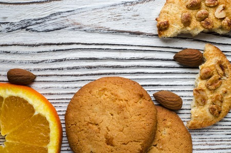 Round orange biscuits with colorful candied fruits and a slice of juicy orange lying on a wooden table. Closeup