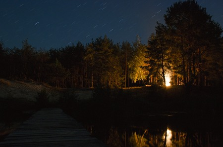 Bonfire in the night forest. Wooden bridge over the river that leads into the Woods