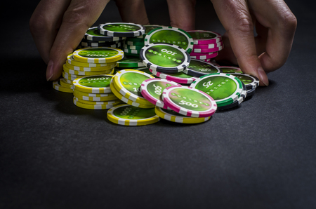 On the black table lie poker chips, cards and a dealer chip. Man's hand holds cards