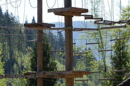 Wooden pillars and hanging ropes of a rope park on the background of green forest in the Carpathians