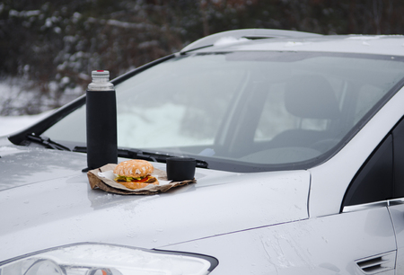 Winter picnic with tea and burger on the hood of a silver car against the background of the winter forest