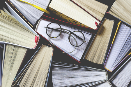 Many multicolored thick open books stand on a dark background. On the books are old round glasses and an open notebook with a pencil. ready to read 免版税图像