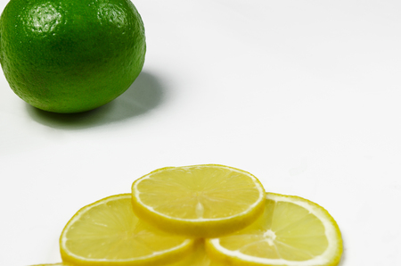 Thinly sliced wedges of lemon and lime green are lying on a white background with copy space top view