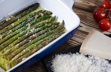Gli asparagi verdi succosi sono in forma di ceramica in olio d'oliva cosparsi di parmigiano e aglio.