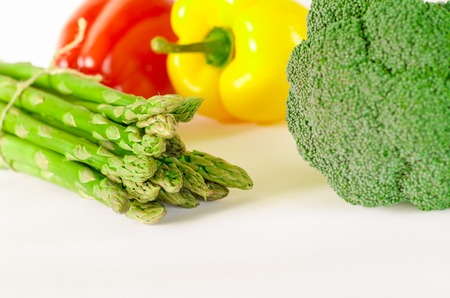 asparagus, Juicy red and orange peppers with a green tail lies next to Bundle of lettuce and broccoli are on a white background. isolated