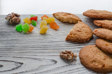 Round orange biscuits with colorful candied fruits and a slice of juicy orange lying on a wooden table against the background of winter snow-covered forest.