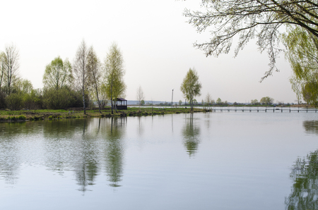 A place for meditation-wooden gazebo stands on the shore of the Lake near the young trees. Spring