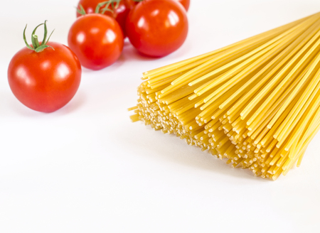 Spaghetti lie on a white background, along with cherry tomatoes, a spoon and a fork