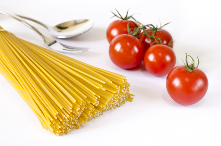 Spaghetti lie on a white background, along with cherry tomatoes, a spoon and a fork Фото со стока - 122227998