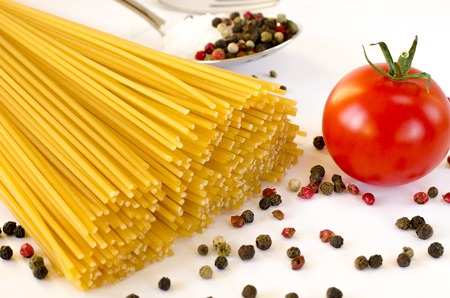 Spaghetti lie on a white background, along with cherry tomatoes, a spoon and a fork Фото со стока - 122228000
