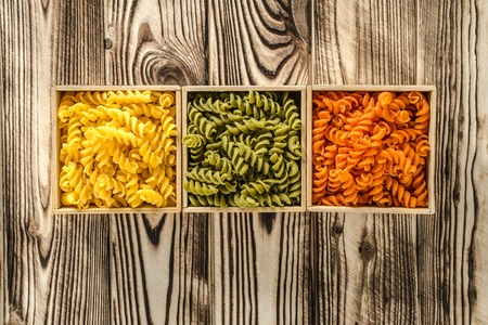 Multi-coloured pasta in the form of spirals lies in square wooden boxes that stand on a wooden table