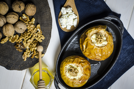 Baked apples with cottage cheese and nuts lie in a black baking dish on a black wooden table next to a jar of honey and a wooden board on which nuts lie. close-up