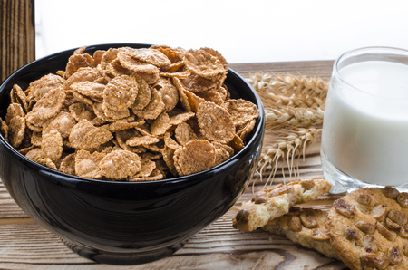 Cereal flakes lie in a black plate, which stands on a wooden table next to a glass of milk, biscuits and ears of wheat against the background of a winter forest