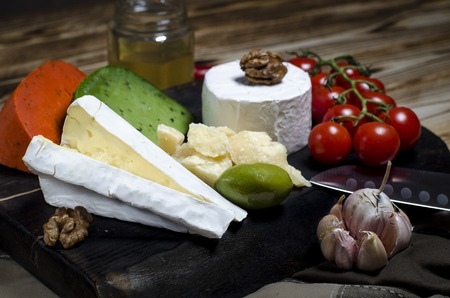 Camembert, brie, parmesan cheese, green cheese with basil and red chilli cheese lie on a dark board next to tomatoes, olives, garlic, nuts and honey on a wooden table