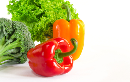 Juicy red and orange peppers with a green tail lies next to Bundle of lettuce and broccoli are on a white background. isolated Фото со стока