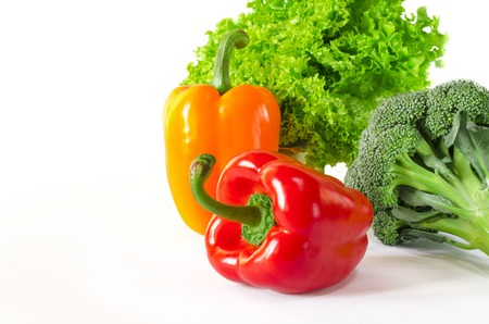 Juicy red and orange peppers with a green tail lies next to Bundle of lettuce and broccoli are on a white background. isolated Фото со стока - 122228124