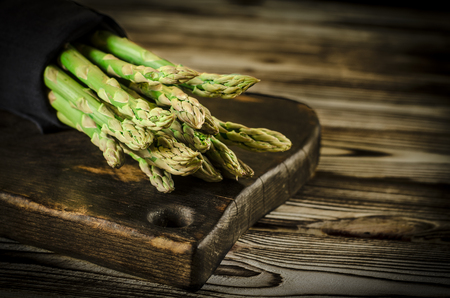 Green juicy asparagus is lying on a wooden dark board on a brown wooden table.