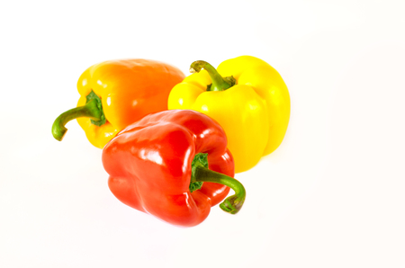 Juicy red, orange and yellow peppers with a green tail lies on a white background. isolated Фото со стока - 122228128