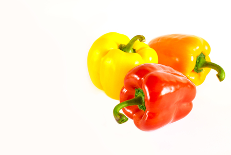 Juicy red, orange and yellow peppers with a green tail lies on a white background. isolated
