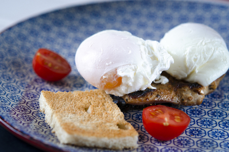 good morning. Delicious breakfast with Eggs Benedict with meat steak, tomatoes and toast lying on a blue plate
