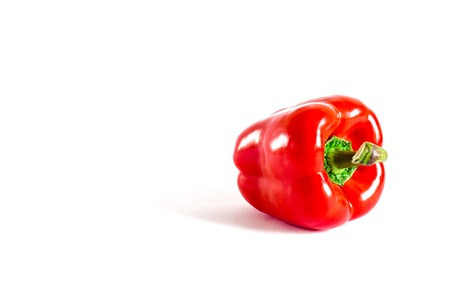 Juicy red pepper with a green tail lies on a white background